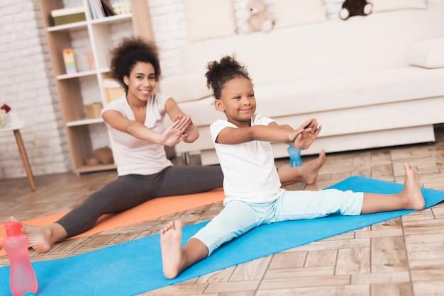 Mamá e hija están haciendo yoga en casa.