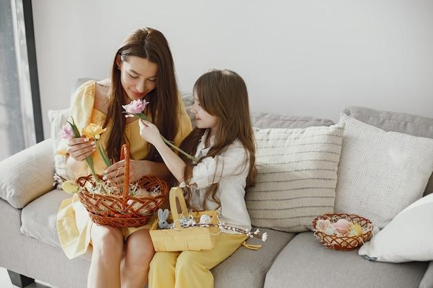 Mamá e hija se están preparando para la pascua en casa en el sofá con ropa amarilla