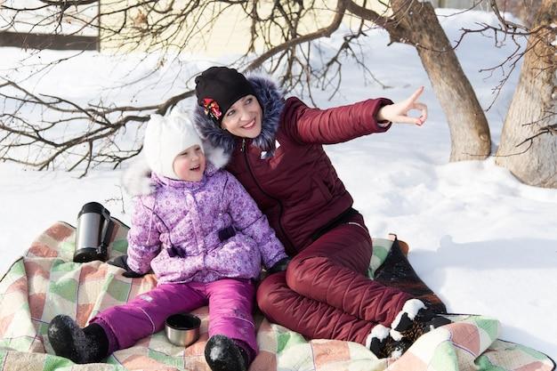 Mamá e hija están sentadas en una tela escocesa en la nieve en invierno.