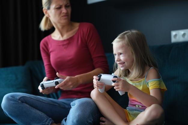 Mamá e hija juegan juegos en línea en primer plano de la consola