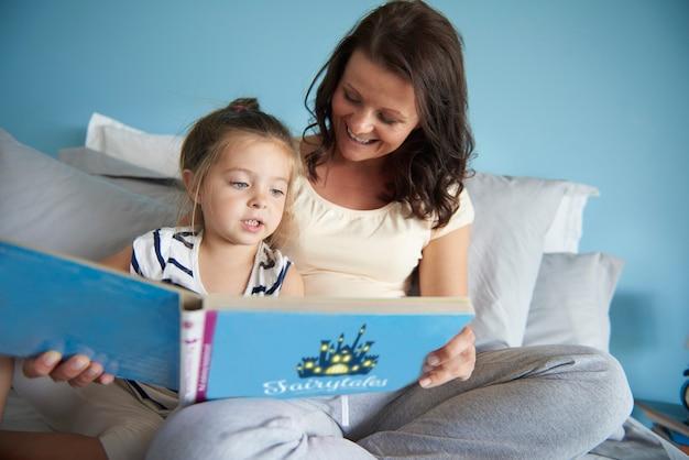 Mamá e hija leyendo algunos cuentos de hadas.