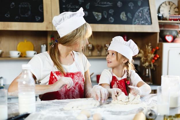 Mamá e hija con la misma ropa se divierten preparando una masa en una cocina acogedora