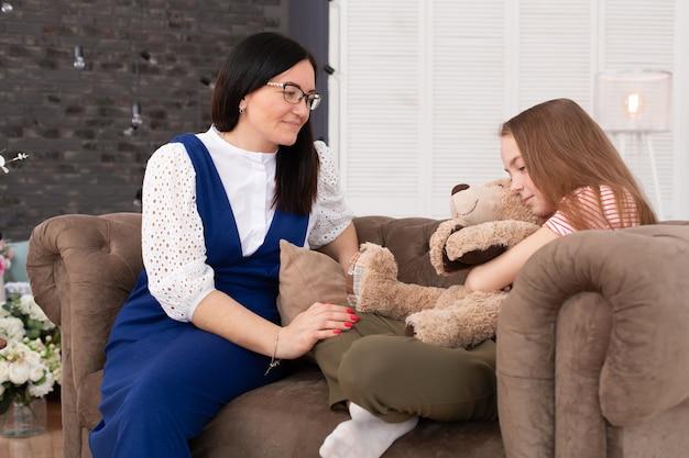 Mamá e hija pasan tiempo juntas, se sientan en el sofá y conversan.