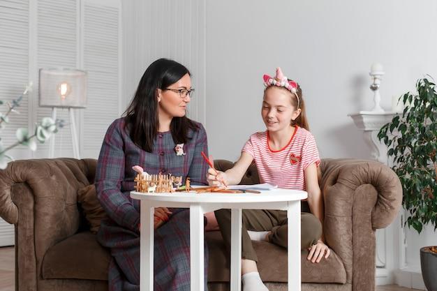 Mamá e hija pasan tiempo juntas, se sientan en el sofá, hablan y dibujan con lápices de colores.