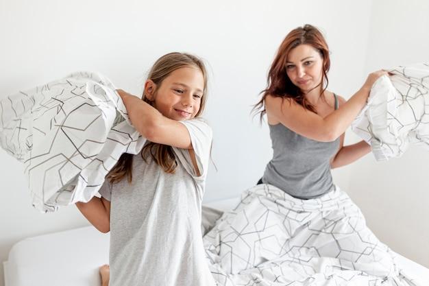 Mamá e hija pelea de almohadas