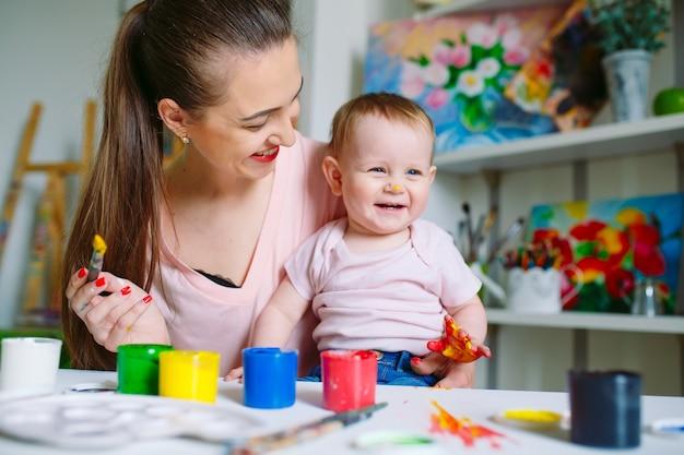 Mamá e hija pintan sobre lienzo en la escuela de dibujo