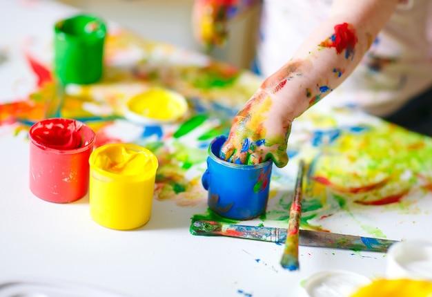 Mamá e hija pintan sobre lienzo en la escuela de dibujo.