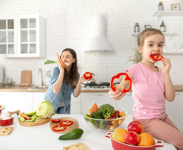 Mamá e hija preparan una ensalada en la cocina. diviértete y juega con verduras