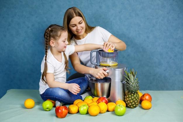 Mamá e hija preparan una naranja fresca. están en camisetas blancas.