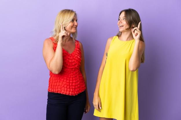 Mamá e hija que intentan darse cuenta de la solución mientras levantan un dedo