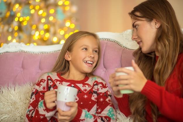Mamá e hija sentadas en el sofá y hablando