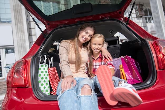Mamá e hija sonrientes abrazándose, sentados en el maletero del coche