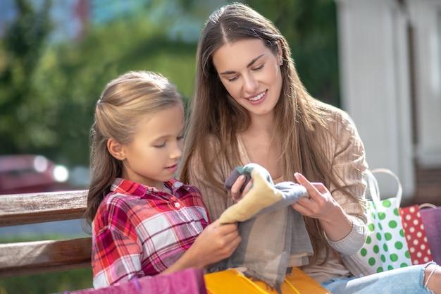 Mamá e hija sonrientes sentados en un banco del parque, admirando la nueva bufanda