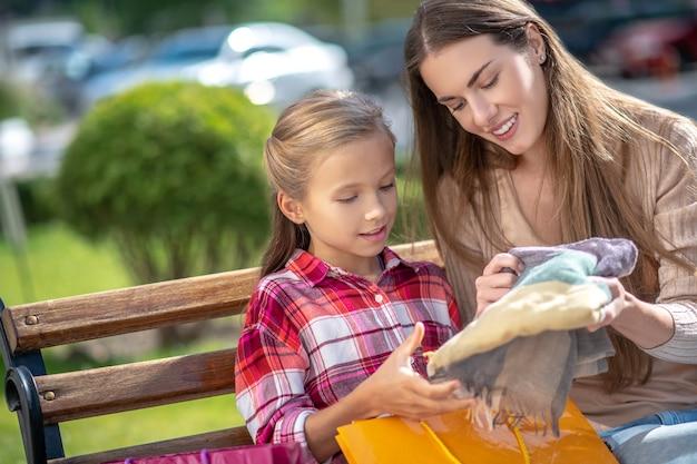 Mamá e hija sonrientes sentados en un banco del parque, mirando bufanda