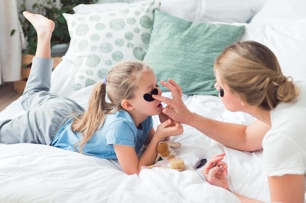 Mamá e hija usando parches para los ojos y cepillo para el cuidado de la piel facial spa y proceso de cuidado corporal
