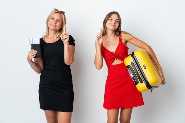 Mamá e hija van a viajar mostrando y levantando un dedo en señal de lo mejor