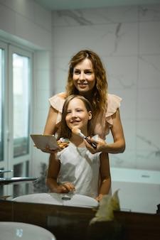 Mamá e hijas hacen maquillaje en el baño, aplican lápiz labial frente al espejo.