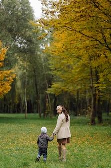 Mamá e hijo caminando y divirtiéndose juntos en el parque de otoño.