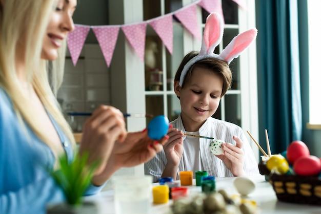 Mamá e hijo decoran huevos de pascua en la cocina.