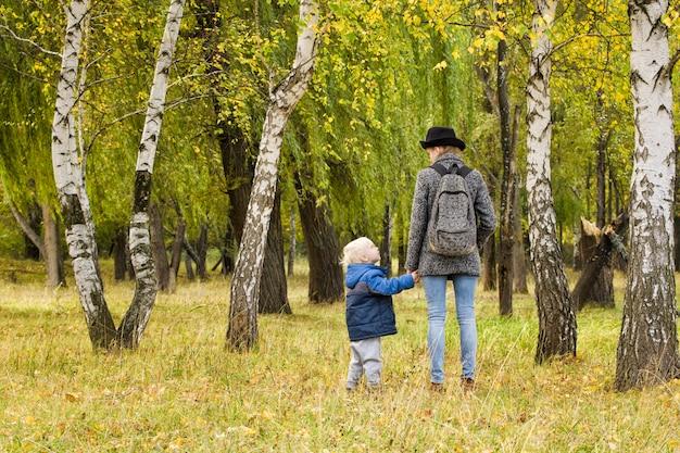 Mamá e hijo están caminando en el bosque de otoño. vista desde atrás