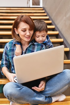 Mamá e hijo están haciendo la tarea en la computadora. concepto madre e hijos, tecnología moderna e internet.