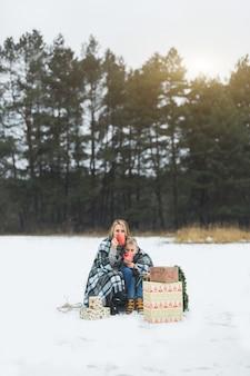 Mamá e hijo pasan tiempo juntos en el día de invierno, cubiertos con cuadros, sosteniendo tazas con bebidas calientes