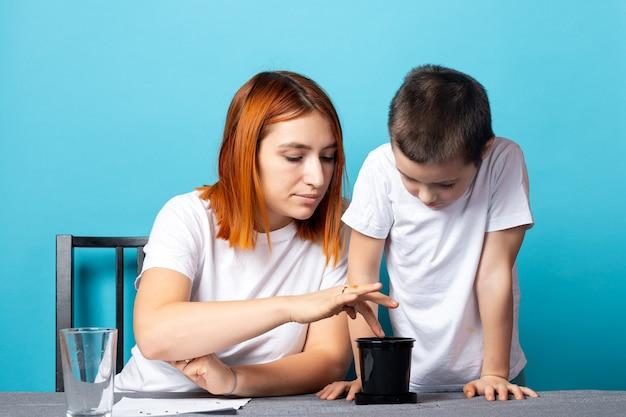 Mamá e hijo ponen tierra en una maceta negra para plantar una semilla y hacer crecer una planta de interior en la mesa.