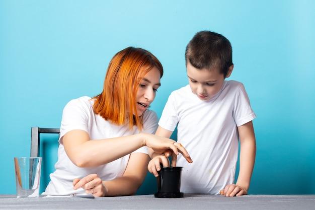 Mamá e hijo ponen tierra en una maceta negra para plantar una semilla y hacer crecer una planta de interior sobre la mesa sobre un fondo azul.