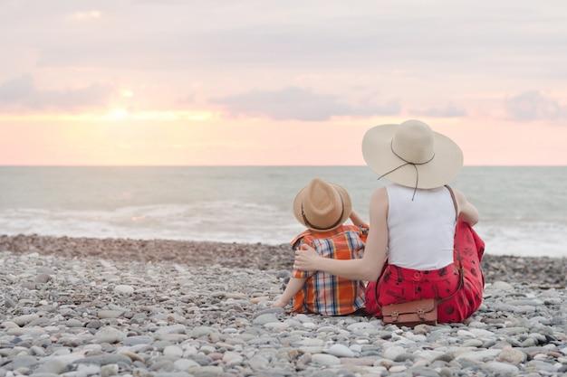 Mamá e hijo sentados en la playa y admirar la puesta de sol