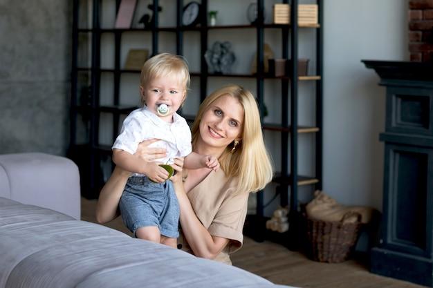 Mamá e hijo se sientan en el sofá mirando a la cámara y sonriendo