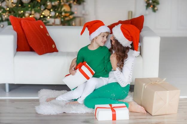 Mamá e hijo con trajes de año nuevo y buen humor posando delante de la cámara el día de año nuevo