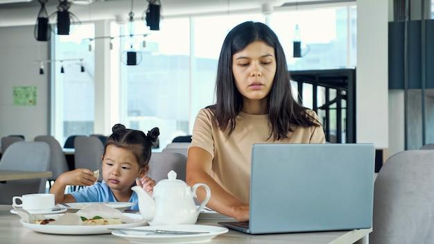 Mamá empresaria asiática trabaja sentada a la mesa con té y una computadora portátil gris y el niño come una rebanada de pizza para un niño pequeño