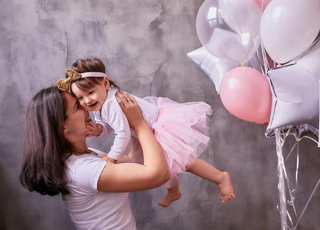 Mamá encantadora sostiene a su hijita tierna de pie en la habitación.