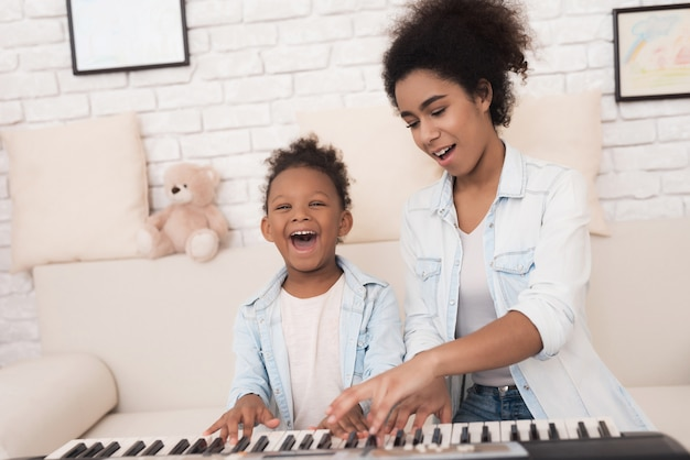 Mamá enseña a una niña a tocar el piano.