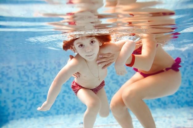 Mamá le enseña a un niño a nadar en la piscina