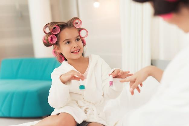 Mamá enseña a una pequeña hija a hacer maquillaje.