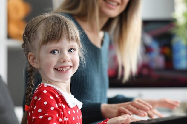 Mamá le enseña a su hija a tocar el piano electrónico