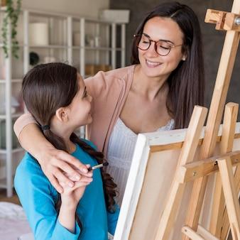 Mamá enseñando a niña a pintar en casa