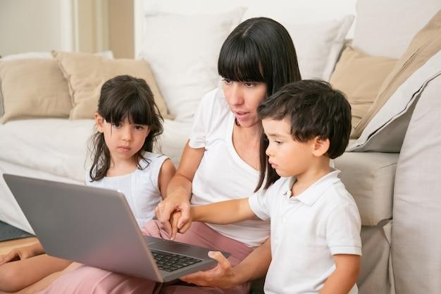 Mamá enseñando a los niños a usar la computadora portátil, sosteniendo la mano del pequeño hijo y presionando el botón del teclado con el dedo del niño.