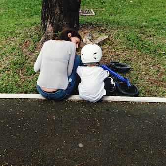 Mamá enseñando a su hijo a andar en bicicleta al aire libre