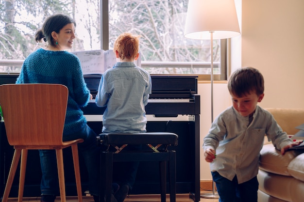 Mamá enseñando a su hijo en casa lecciones de piano. estilo de vida familiar pasar tiempo juntos en el interior. niños con virtud musical y curiosidad artística.