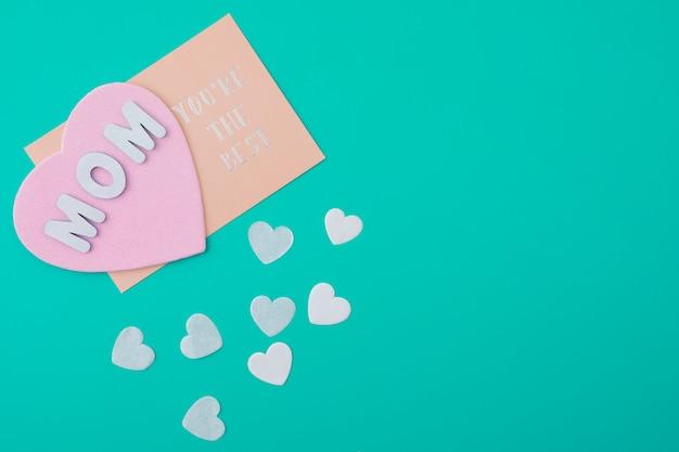 Mamá eres la mejor inscripción con corazones de papel pequeños.