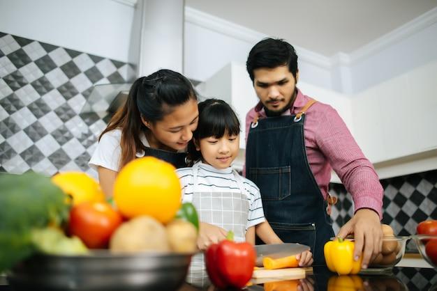 Mamá feliz le enseña a su hija a picar vegetales preparando ingredientes