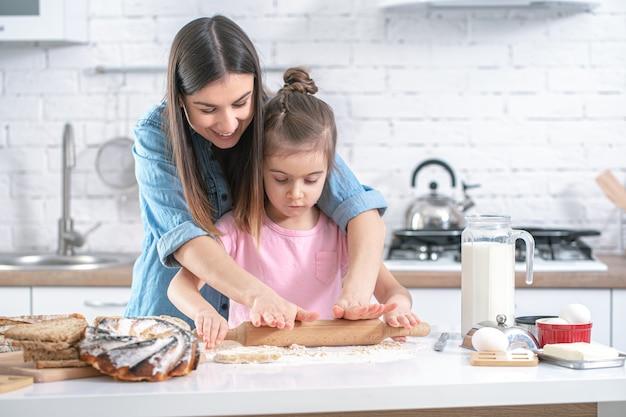 Mamá feliz con hija preparando pasteles caseros en el fondo de una cocina ligera.