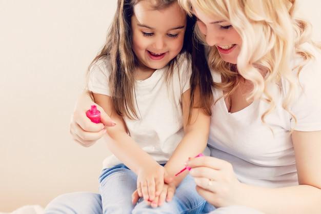 Mamá feliz y una niña pequeña sentadas en casa juntas y haciendo una pausa sus propias uñas
