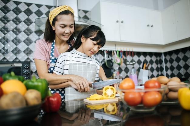 Mamá feliz que enseña a su hija que prepara y que taja la verdura para cocinar.