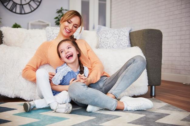 Mamá feliz y su pequeña hija divirtiéndose en casa