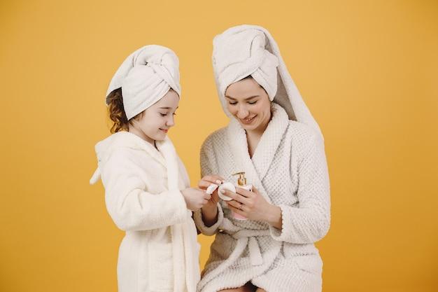 Mamá con hija. chicas con albornoces blancos. mamá enseña a su hija a maquillarse.