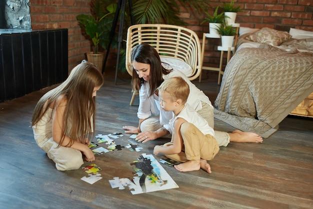 Mamá, hija e hijo armaron el rompecabezas en el suelo. entretenimiento familiar. mujer, niña y niño juegan juntos