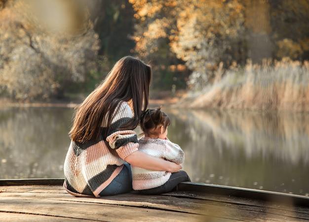Mamá con hija pequeña en bosque otoñal.